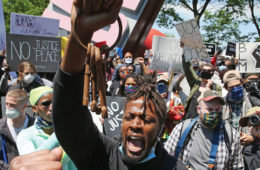 Photo of a crowd gathered at a Cleveland Black Lives Matter protest, with a focus on a Black man in front holding a set of keys