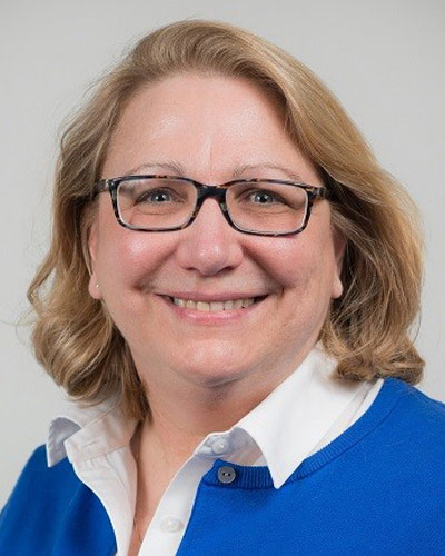 Photo of faculty member wearing glasses and bright blue sweater over white shirt
