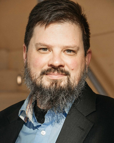 Faculty member with mustache and beard, wearing blue button-down shirt and black jacket