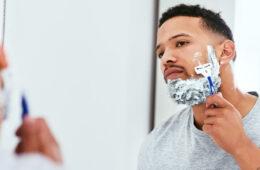 Photo of a man shaving his beard in a mirror