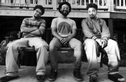 Black and white photo of the three members of Muamin Collective sitting on a bench