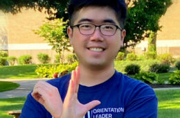 Photo of Yuliang (Bill) Ding posing for photo and making an O and an L with his hands