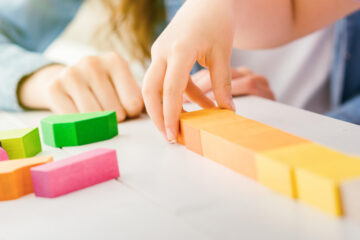 Close-up photo of a child playing with colorful toy blocks and a caregiver sitting next to her