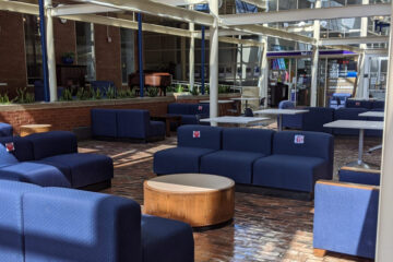 Photo of the Thwing Center atrium with a hand sanitizing station and couches with spaces marked off