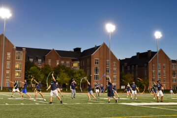 Orientation leaders dance during with streamers during the traditional Boogie on the football field