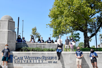 Socially distanced students pose for a photo with CWRU signage outside of the Maltz Performing Arts Center