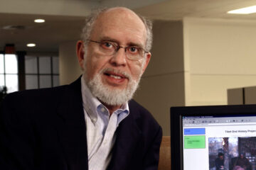 Photo of Melvyn Goldstein posing next to a computer screen with the webpage for the Center for Research on Tibet pulled up