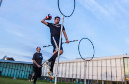 Photo of a student leaping into the air with a ball in his hand to throw it through a hoop as two others look on during quidditch practice