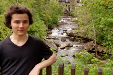 Photo of Christopher Lysyj posing for a photo on a bridge above a river