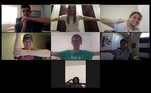 Screenshot of a Zoom meeting with seven students participating in the Human Centered Design class, forming their arms into a combined shape together