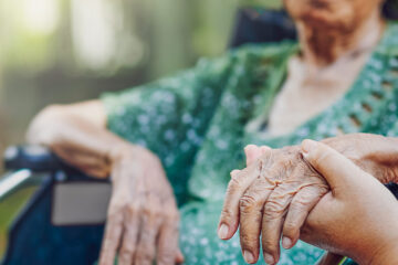 Photo of a nurse in nursing home holding the hand of a female patient
