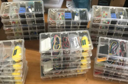 Photo of Arduino-based kits stacked in a table with plastic containers full of electronic materials for students