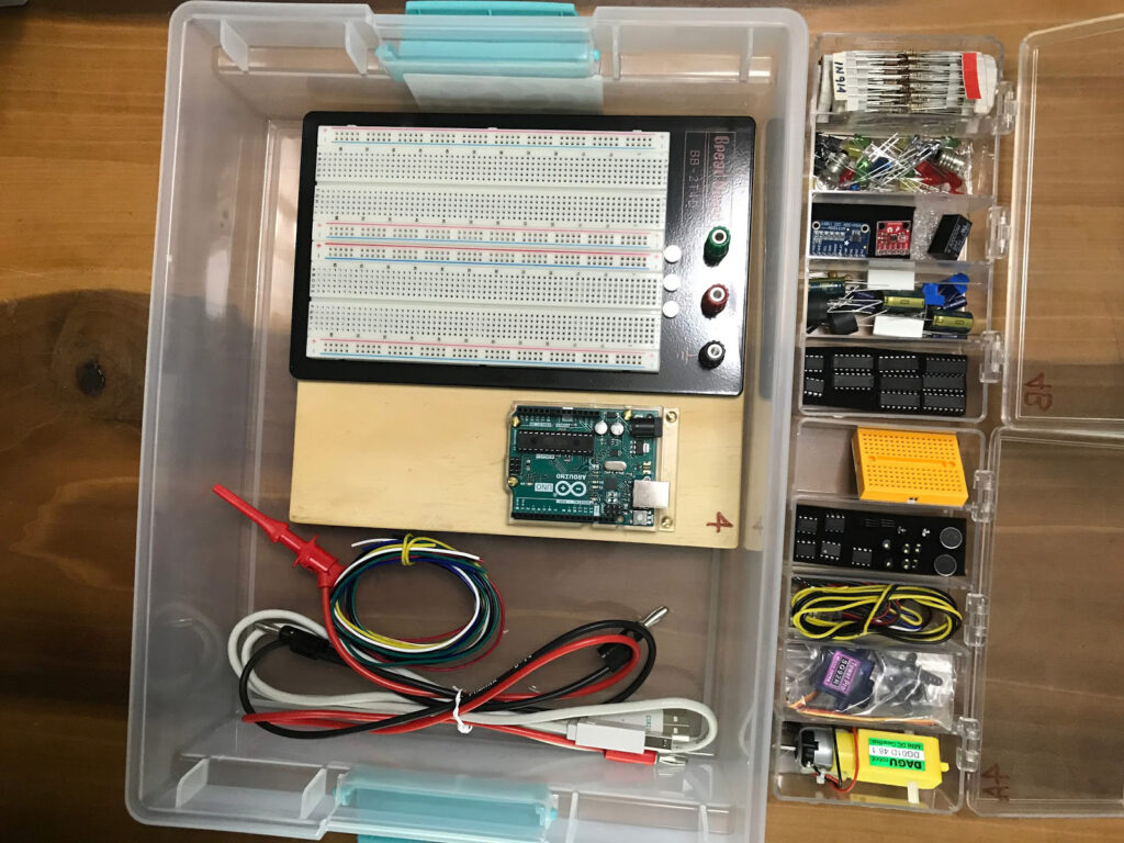 Photo showing the contents of an Arduino-based kit in plastic containers full of electronic materials for students