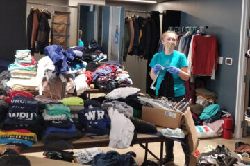 Photo of CWRU student Olivia Paxson wearing a mask and surrounded by stacks of clothes as she organizes donated items for Physical Resource Center