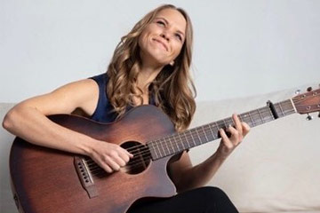 Photo of Diana Chittester playing the guitar