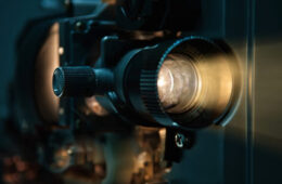 Photo of a film projector shining light through the lens