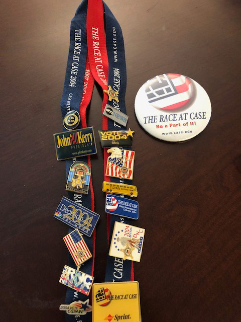 """Photo of lanyards full of political pins next to a button promoting the """"Race at Case"""""""