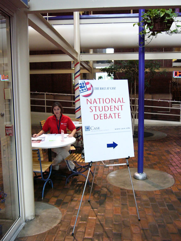 """Photo of a student sitting in Thwing Center next to a sign that says """"National Student Debate"""""""