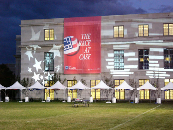 """Photo of stars and stripes projected onto a campus building and a sign hanging that says """"The Race at Case"""""""
