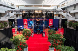 Photo of the courtyard of the Samson Pavilion with red carpet covering the floor, trees in planters surrounding the area and the debate stage with lights overheads