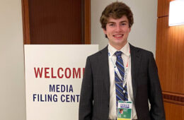 "Photo of Nathan Lesch in front of a sign that says ""welcome media filing center"""
