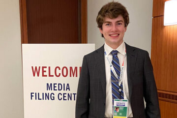"""Photo of Nathan Lesch in front of a sign that says """"welcome media filing center"""""""