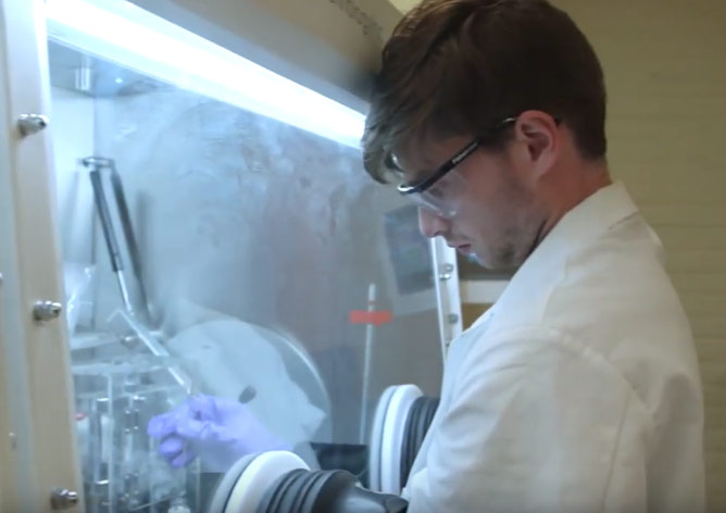 Photo of Henry Squire working in a lab using protective gear