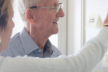 Elderly man and woman looking at reminder notes