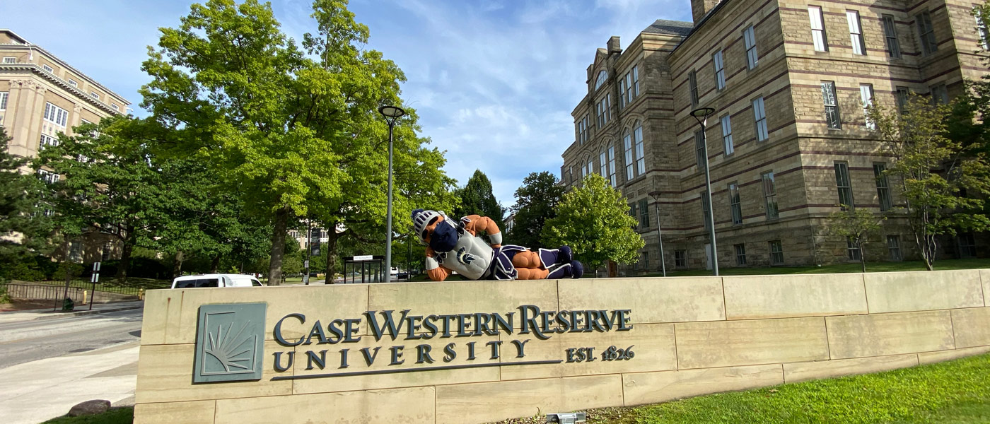 Photo of Spartie wearing a mask while laying on the CWRU sign in front of Adelbert Hall