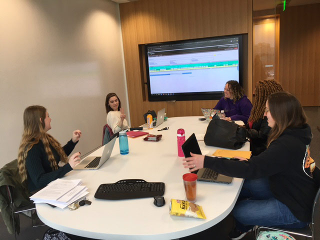 Photo of five students sitting around a conference table