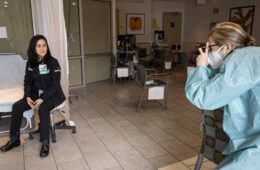 Photo of Janine Llamzon posing for a photo in a hospital setting as a photographer takes a picture