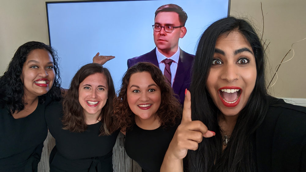 Four alumni pose for a photo with another alum on a TV screen