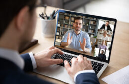 Photo of a man typing on a keyboard during a virtual meeting