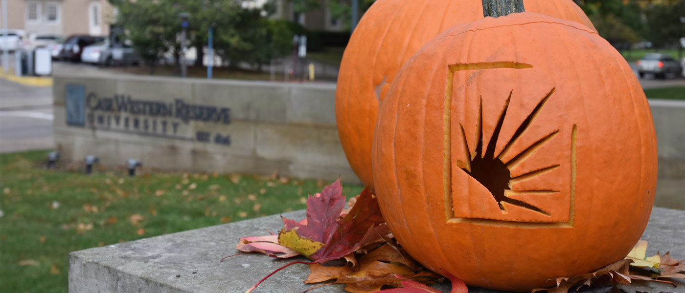Photo of two pumpkins, one carved with CWRU sunburst logo, with CWRU sign in the background