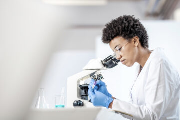 Photo of a researcher in the lab looking into a microscope