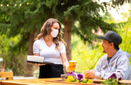 Photo of a waitress wearing a mask serving a man seated at a table