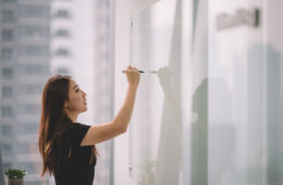 Photo of a woman writing on a whiteboard with a marker