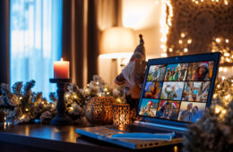 Photo of an open laptop on a table among festive holiday decorations
