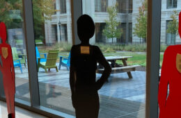 Photo of life-sized red and black wooden figures at Tinkham Veale University Center