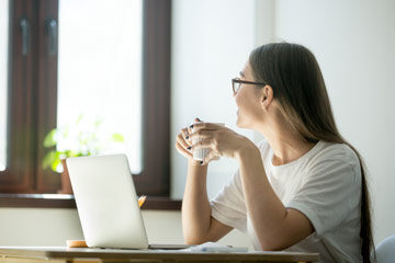Photo of a woman smiling looking out a window and holding a cup of coffee while sitting out a laptop