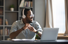 Photo of a smiling man sitting at a desk with a laptop and headphones in