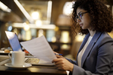 Photo of a woman reading a paper in front of a computer