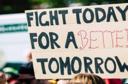 "Photo of someone holding a sign that says ""fight today for a better tomorrow"" during a protest"