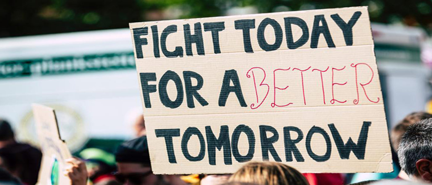 """Photo of someone holding a sign that says """"fight today for a better tomorrow"""" during a protest"""