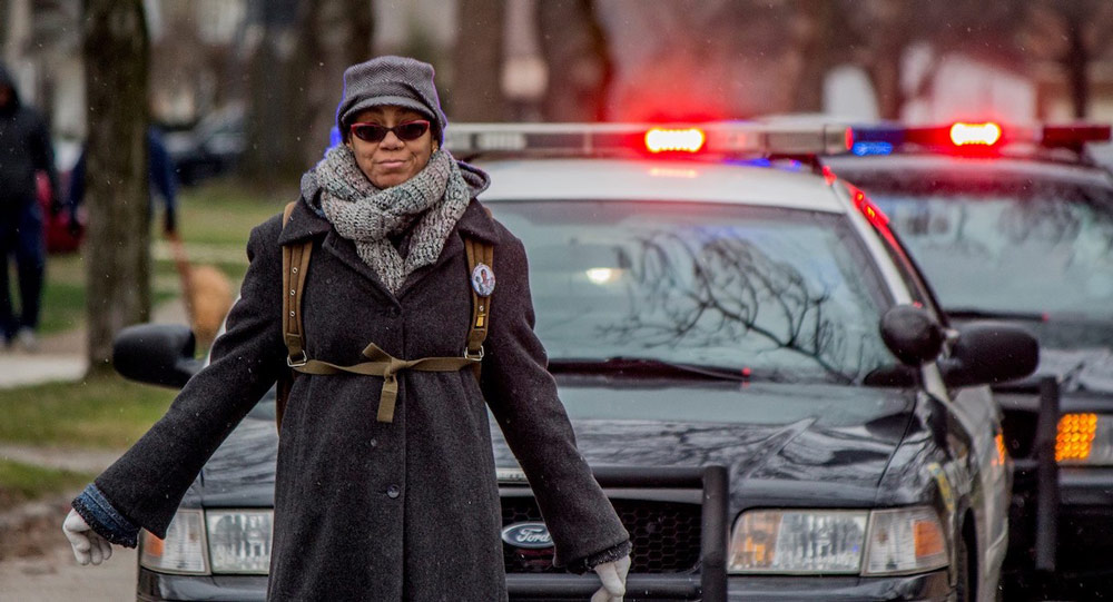 Photo of Rhonda Williams walking in a protest with police cars behind her