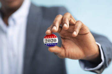 Close up photo of a man holding a 2020 pin