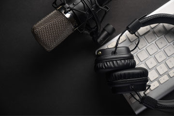 Photo of a microphone, headphones and a keyboard sitting on a surface
