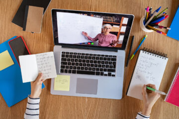 Photo of an open laptop and female hands taking notes