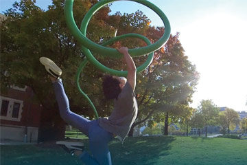 Photo of a student dancing alongside a sculpture on the CWRU campus