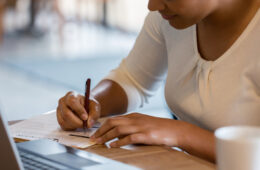Photo of a woman writing on a paper in front of a laptop
